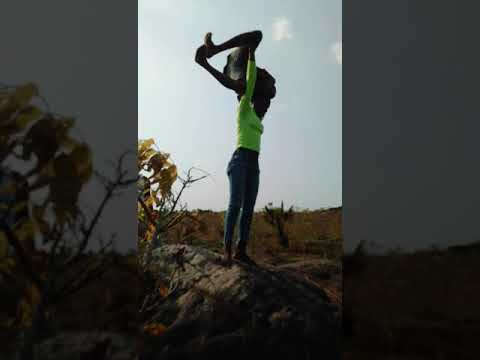 Strong African girl does a very risky overhead lift and carry on a shapeless high rock shorts